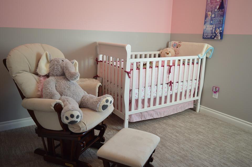 חדר ילדים בנות בצבע ורוד עם עריסה ודובי על כיסא