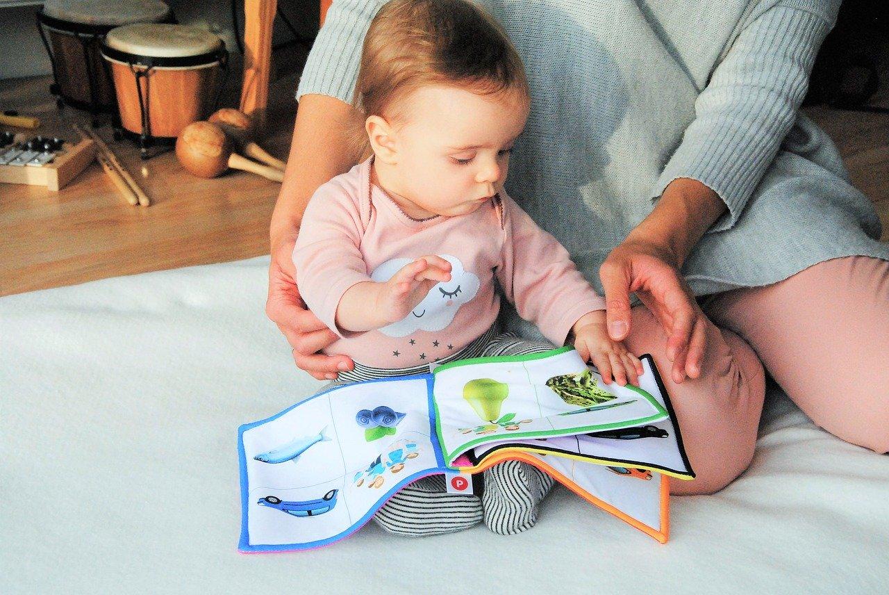 עיצוב חדרי תינוקות עם תינוקת על הרצפה קוראת ספר